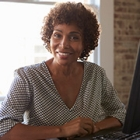 Smiling African American businesswoman sitting at a desk in front of a computer